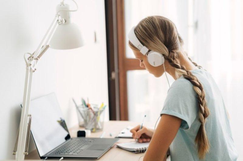 Dievča sedí za počítačom a píše si poznámky