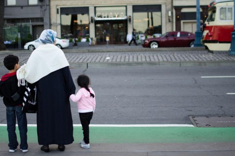 Matka drží svoje deti za ruku na ulici
